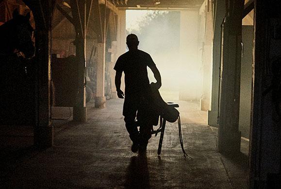 silhouette of war veteran holding saddle walking through barn
